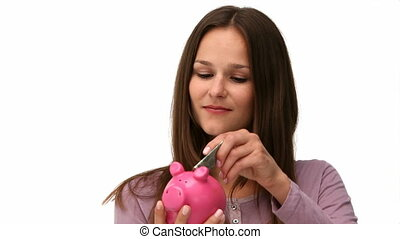 Woman putting money into a piggybank - Woman putting money...