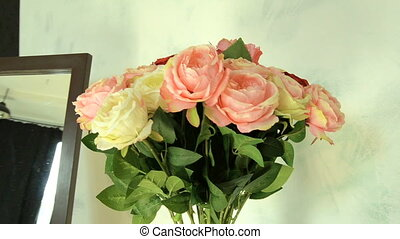 beautiful bouquet of tender roses stands in a vase on a...