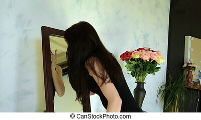 girl with long black hair stands before the mirror and doing...