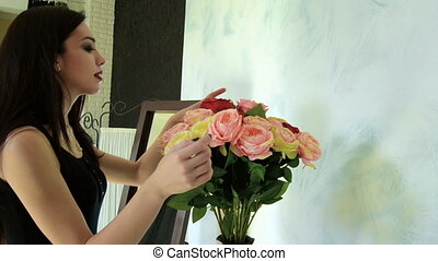 charming brunette smiles and pulls out a vase flower...