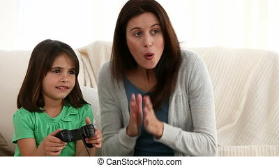 Mother encouraging her daughter while playing video games at...