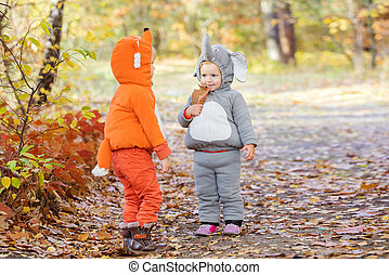 Little children in animal costumes playing in autumn forest...
