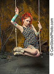 Tattooed girl with orange dreadlocks on the swing - The...