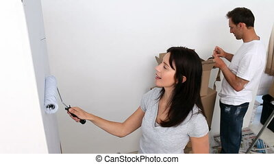 Couple renovating their bedroom painting walls in white