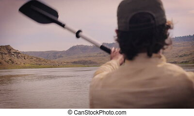 Man paddling down the Missouri river in Montana wearing a...