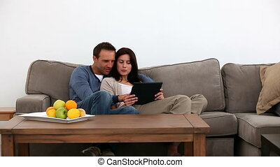 Couple using their pda together on the sofa at home