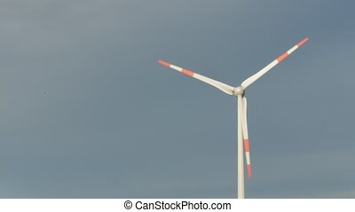 Regular wind turbines rotating in the wind on an blue sky. -...