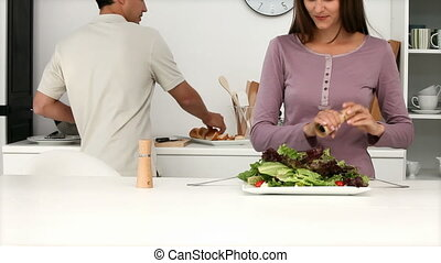 Young couple preparing salad in the kitchen