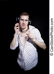 young man listening to music through headphones on black...