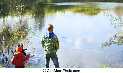 Children stand on the shore of the pond and throw stones. Walks in the fresh air
