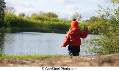 A child stands on the Bank of the pond and throwing stones. Walks in the fresh air