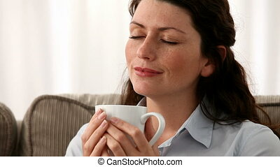 Pretty woman smelling her coffee sitting on the sofa