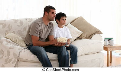 Father and son watching a movie while eating pop corn on the...