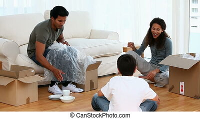 Family playing while unpacking in their living room