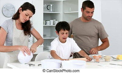 Cute family baking cakes together in the kitchen