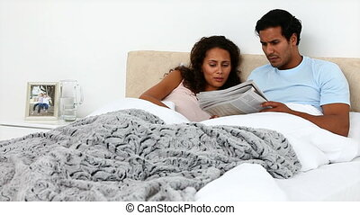 Reaxed couple reading the newspaper