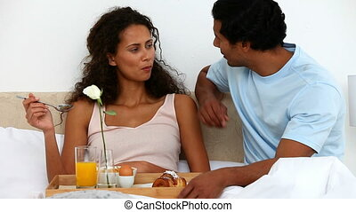 Cute woman having breakfast on bed with her husband
