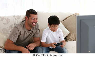 Happy dad encouraging his son while playing video games in...