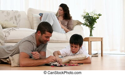 Father and son playing checkers while mother relaxing on the...