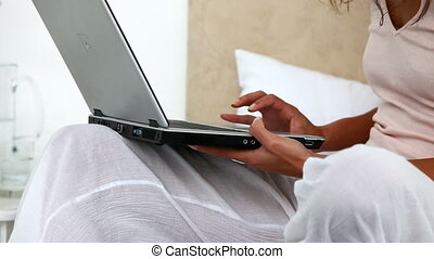 Woman on her bed with laptop during the morning at home
