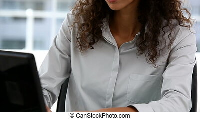 Beautiful businesswoman working on her laptop sitting at her...