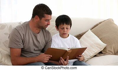 Father and son reading together on the sofa at home