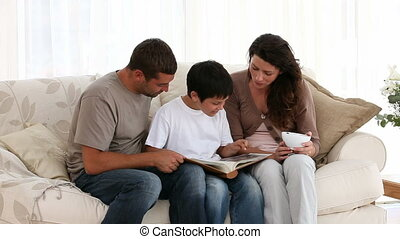 Little boy looking at a photo album with his parents in...