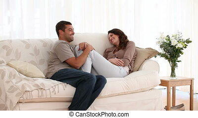 Lovely couple talking on the sofa at home