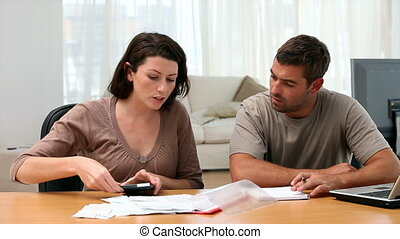 Couple doing their accounts sitting at a table in the living...