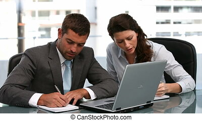 Man and woman working on a laptop sitting at a table in...