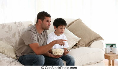 Attentive father watching tv with his son in the living room