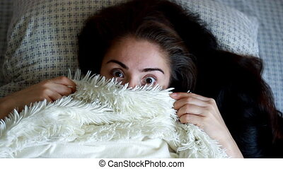 The girl lies on the bed and closes her blanket from fright,...