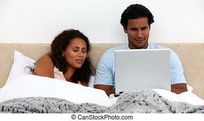 Couple with laptop on their bed during a weekend at home