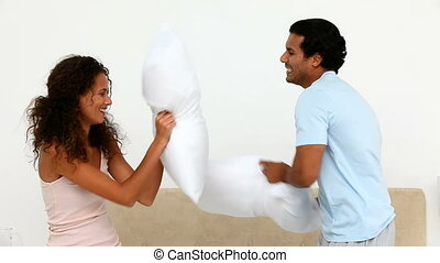 Lovely couple doing a pillow fight on their bed