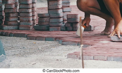 Worker is Laying Paving Stones using Hammer