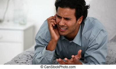 Furious man on the phone lying on his bed at home
