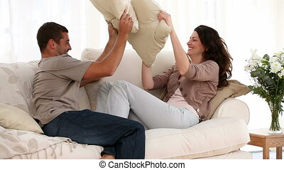 Couple doing a pillow fight on the sofa at home