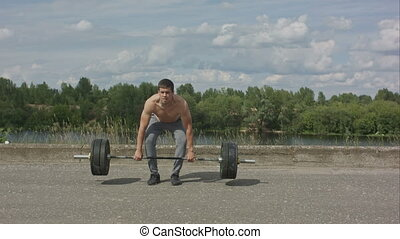 Bodybuilder doing barbell weight workout deadlift with heavy...