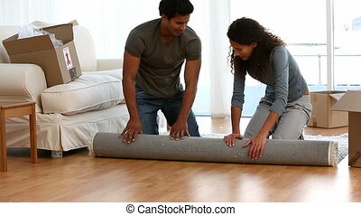 Latin couple rolling a carpet during their removal