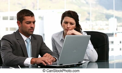 Charismatic business people working on a laptop sitting at a...