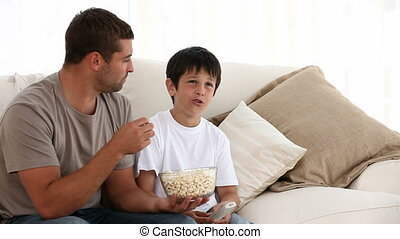 Cute little boy watching television with his father on the...