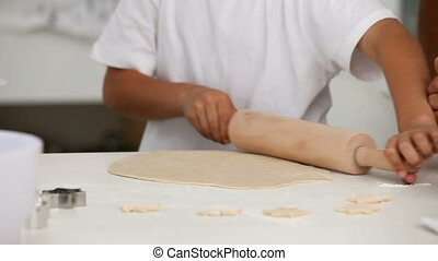 Young boy using a rolling pin with his parents in the...