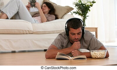 Man reading on the floor while listening music