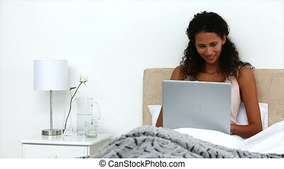Beautiful woman working with laptop in the bed in her...