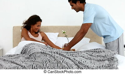 Man bringing breakfast to his girlfriend on the bed at home