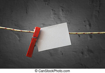 Paper note attach to rope with clothes pins.