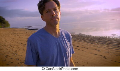 Man motions to camera to stop filming him at the beach -...