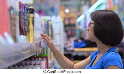 Girl choosing haircare product in the store - Young brunette...