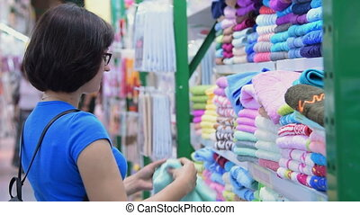 Woman buying towel in the hypermarket - young woman looking...