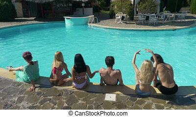 Group of friends sitting by the pool at a private villa waiting for the party to start
